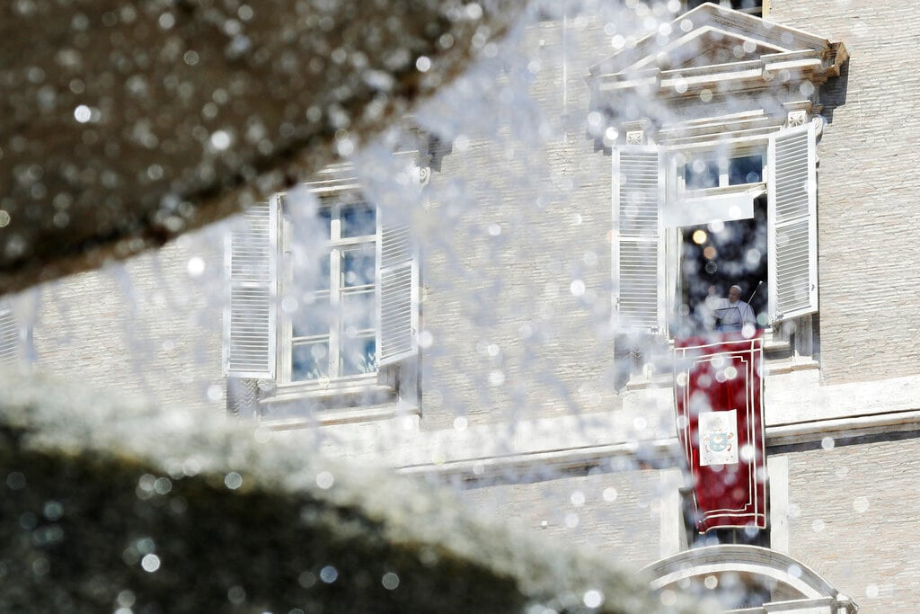 Pope Francis, framed by a fountain, waves to faithful from his studio's window overlooking St. Peter's Square during the Angelus noon prayer at the Vatican, Sunday, Aug. 18, 2019. (AP Photo/Gregorio Borgia)