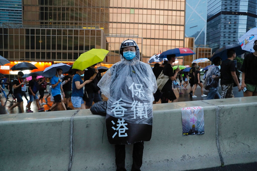 A protester in raincoat wears a sign which reads