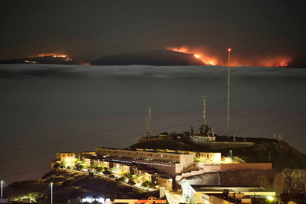 The fire on the mountains of the Canary Islands in this view taken from Santa Cruz de Tenerife island, Spain, early Monday, Aug. 19, 2019. Authorities on Spain's Canary Islands say around 4,000 people have been evacuated due to a wildfire that has ravaged more than 1,700 hectares (4,200 acres) since it broke out a day ago. (AP Photo/Andres Gutierrez)