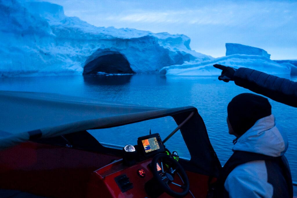 In this Aug. 16, 2019, photo, a boat navigates at night next to a large iceberg in eastern Greenland. Summer 2019 is hitting Greenland hard with record-shattering heat and extreme melt. (AP Photo/Felipe Dana)