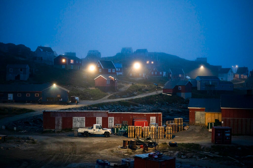 In this Aug. 15, 2019, photo, early morning fog shrouds homes in Kulusuk, Greenland. (AP Photo/Felipe Dana)