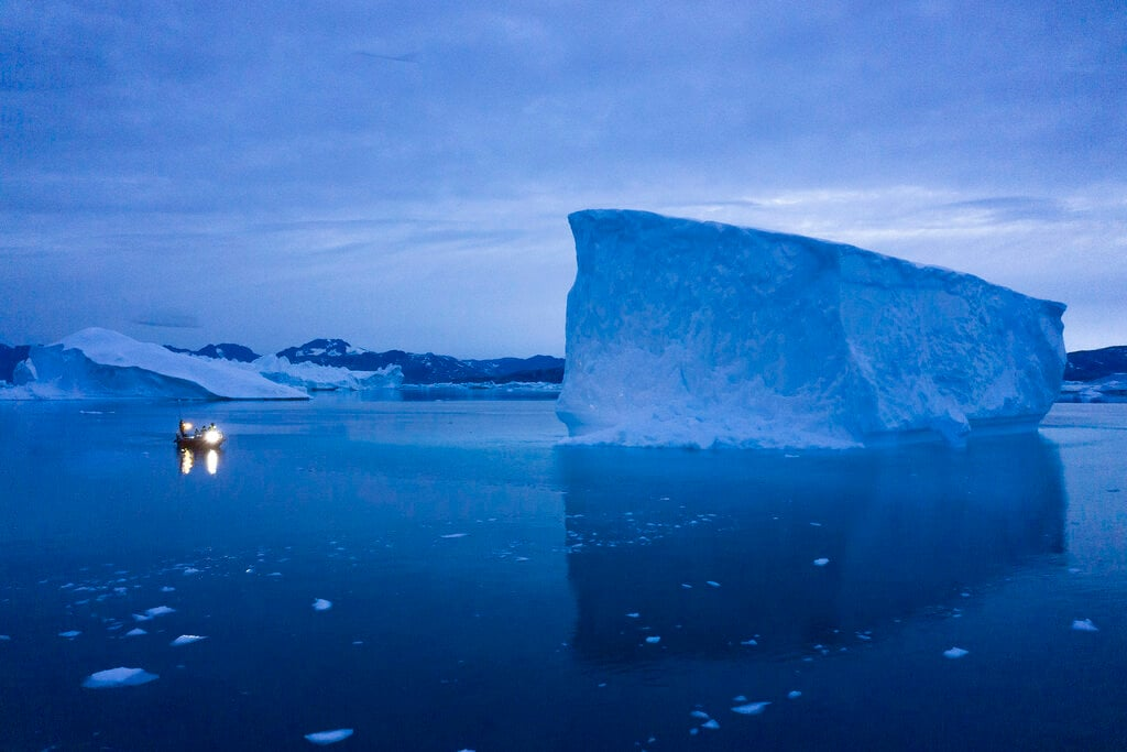 In this Aug. 15, 2019, photo, a boat navigates at night next to large icebergs in eastern Greenland. Greenland's ice has been melting for more than 20 years. (AP Photo/Felipe Dana)