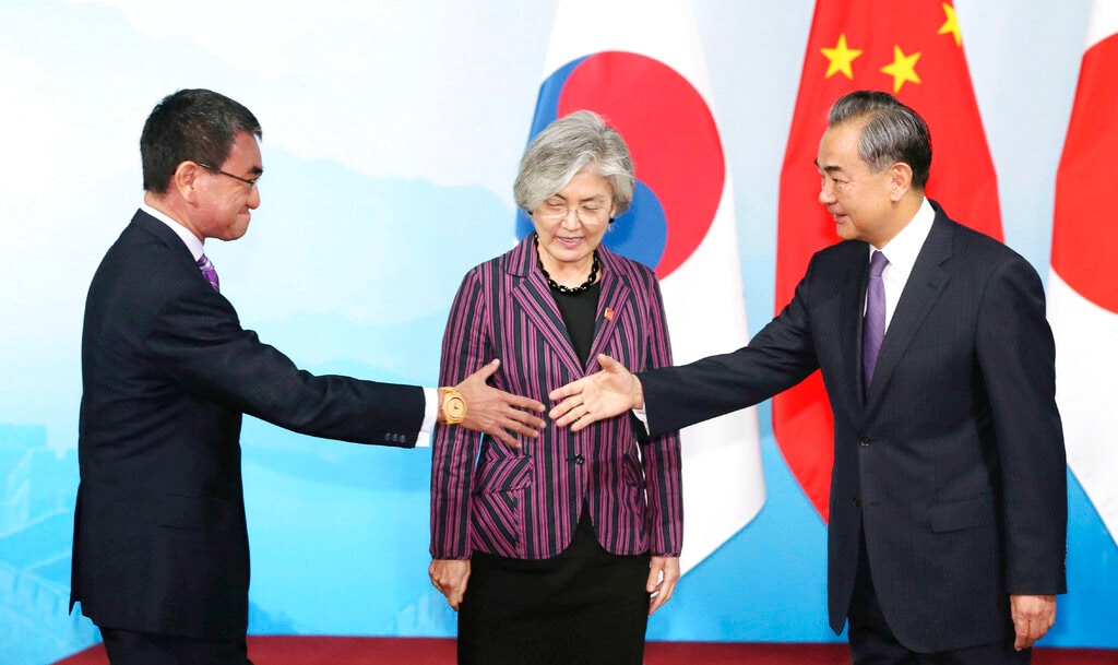 In this Wednesday, Aug. 21, 2019, file photo, Chinese Foreign Minister Wang Yi, right, prepare to shake hands with Japanese Foreign Minister Taro Kono, watched by South Korean counterpart Kang Kyung-wha, center, ahead of their trilateral meeting in Beijing. (Kyodo News via AP, File)