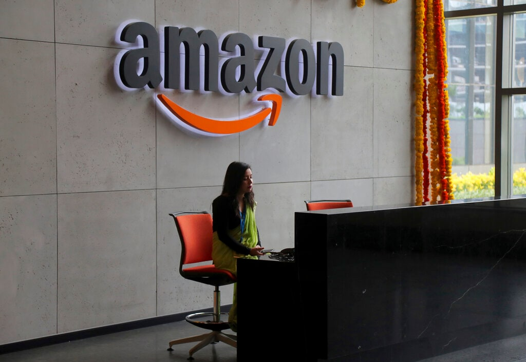 An employee works at the reception desk of Amazon's newly inaugurated campus building in Hyderabad, India, Wednesday, Aug. 21, 2019. (AP Photo/Mahesh Kumar A.)