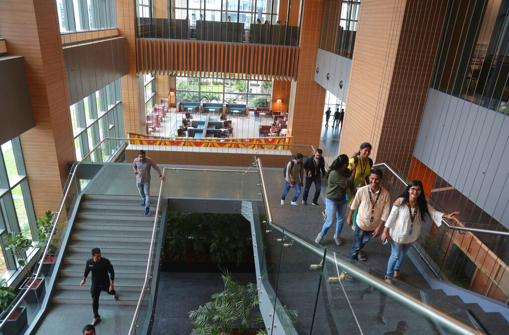 Indian employees walk inside Amazon's newly inaugurated campus building in Hyderabad, India, Wednesday, Aug. 21, 2019. . (AP Photo/Mahesh Kumar A.)