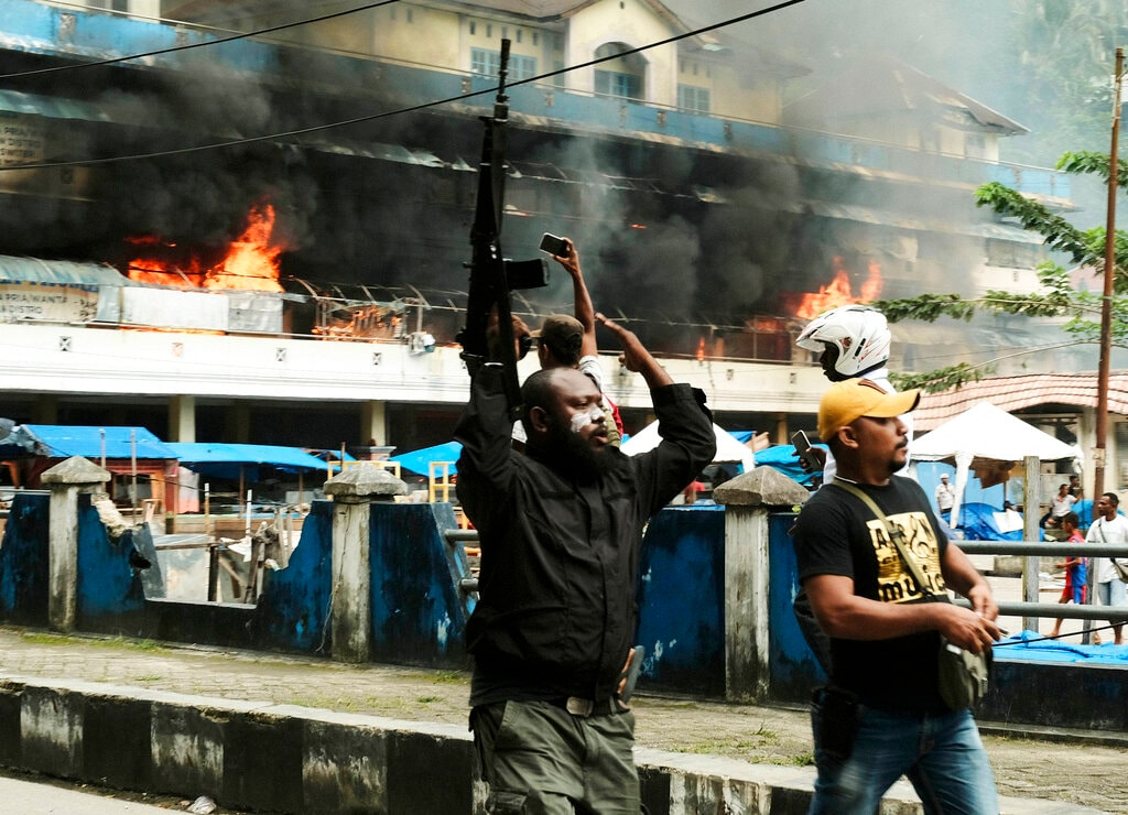 In this Wednesday, Aug. 21, 2019, file photo, a police officer raises his rifle as the local market is seen burning during a protest in Fakfak, Papua province, Indonesia. Indonesia deployed over 1,000 security personnel to the restive province of West Papua amid spreading violent protests sparked by accusations that security forces had arrested and insulted Papuan students in East Java . (AP Photo/Beawiharta, File)