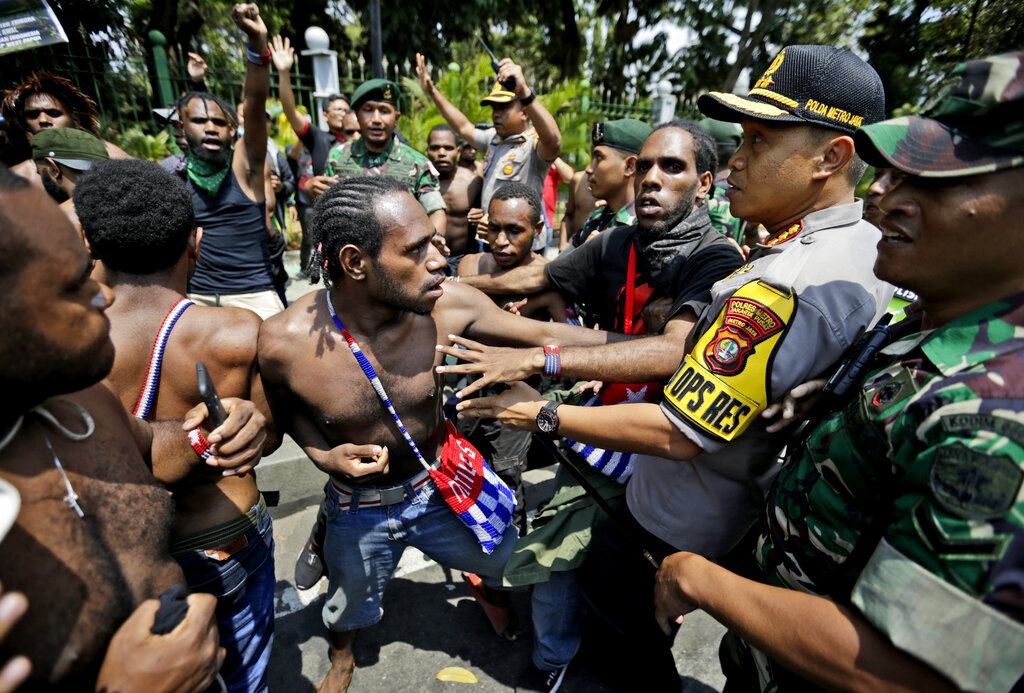 In this Thursday, Aug. 22, 2019, file photo, Papuan activists scuffle with police and soldiers during a rally near the presidential palace in Jakarta, Indonesia. A group of West Papuan students in Indonesia's capital staged the protest against racism and called for independence for their region. (AP Photo/Dita Alangkara, File)