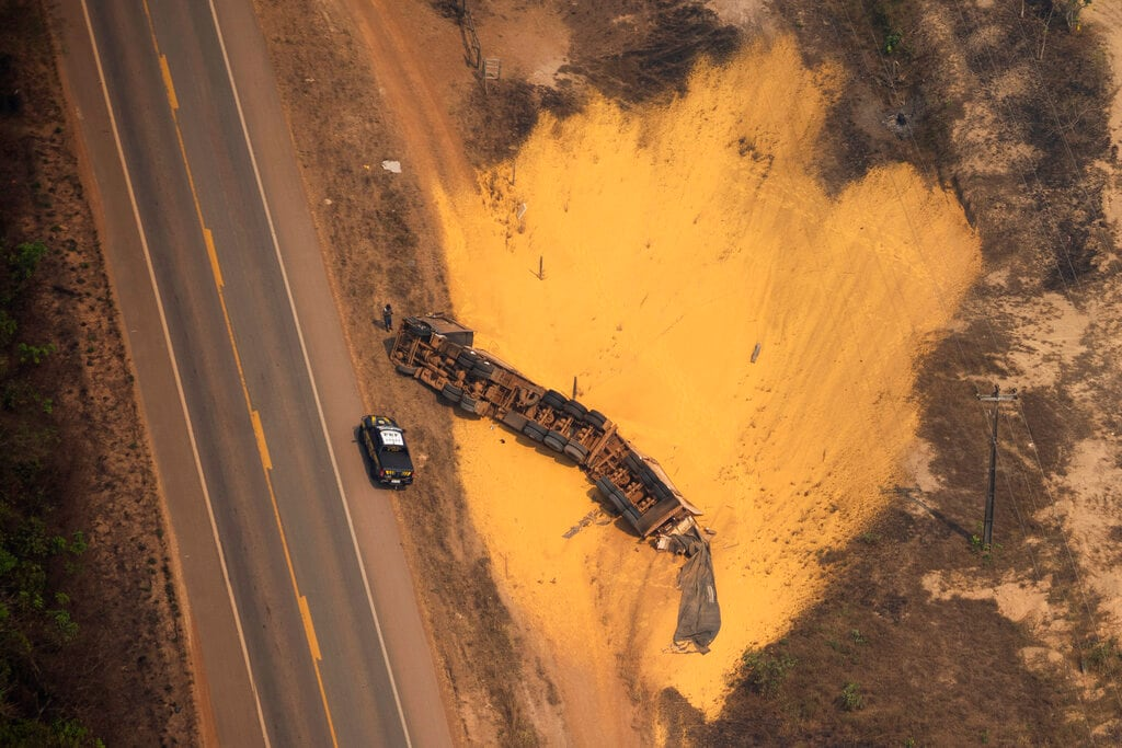A police car sits parked next to an overturned semi-trailer truck that was hauling sand, on a highway near Porto Velho, Brazil, Friday, Aug. 23, 2019. (AP Photo/Victor R. Caivano)