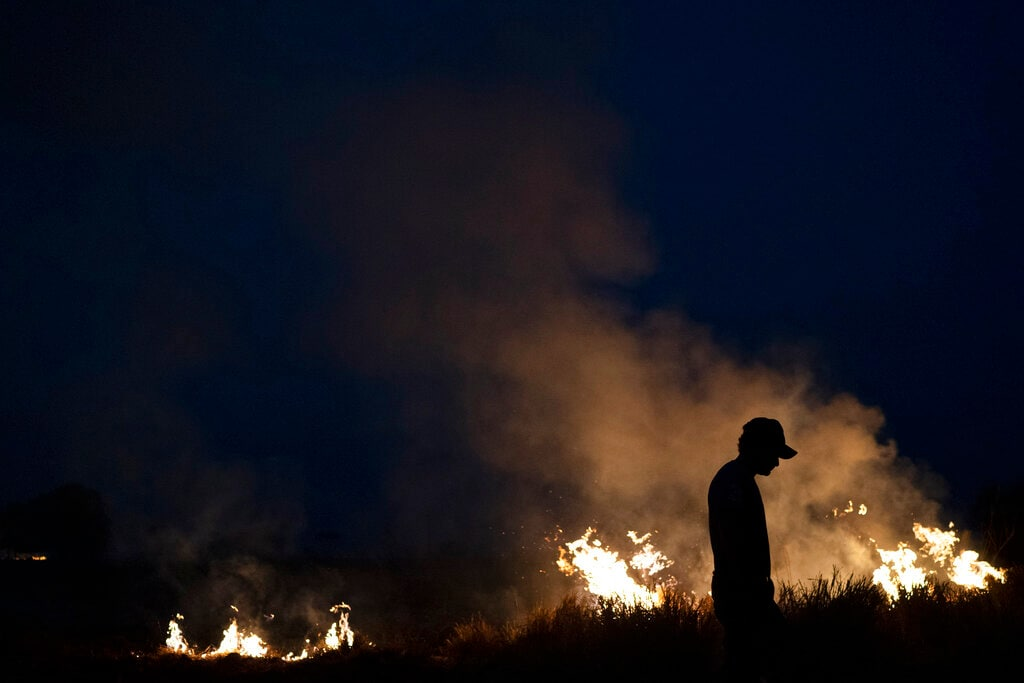 Neri dos Santos Silva, center, is silhouetted against an encroaching fire threat after he spent hours digging trenches to keep the flames from spreading to the farm he works on, in the Nova Santa Helena municipality, in the state of Mato Grosso, Brazil, Friday, Aug. 23, 2019. (AP Photo/Leo Correa)