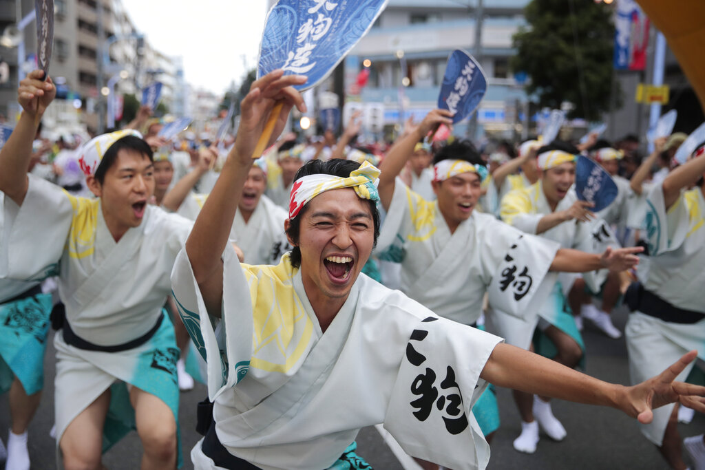 In this Saturday, Aug. 24, 2019, file photo, male dancers entertain spectators at the Koenji Awa-Odori dance festival, in the Koenji neighborhood of Tokyo. Started in the 1950s, the Koenji Awa-Odori has grown to be one of Tokyo's largest and most popular summer festivals with an estimated 10,000 dancers participating in the dance festival. (AP Photo/Jae C. Hong, File)