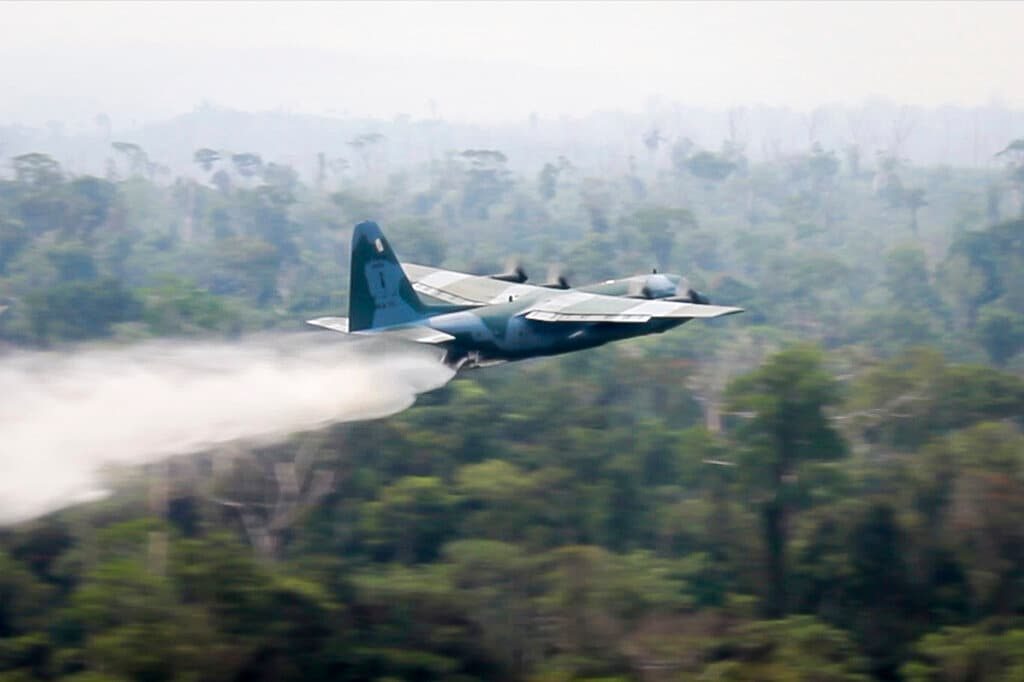 In this photo released by Brazil Ministry of Defense, a C-130 Hercules aircraft dumps water to fight fires burning in the Amazon rainforest, in Brazil, Saturday, Aug, 24, 2019. (Brazil Ministry of Defense via AP)