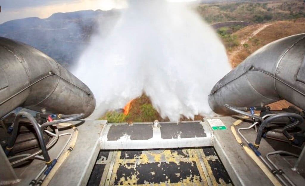 In this photo released by Brazil Ministry of Defense, a C-130 Hercules aircraft dumps water to fight fires raging in Brazil's Amazon, Saturday, Aug, 24, 2019. (Brazil Ministry of Defense via AP)