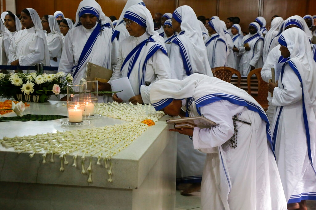 Nuns of the Missionaries of Charity, the order founded by Mother Teresa, pray by her tomb on her birth anniversary in Kolkata, India, Monday, Aug. 26, 2019. During her humanitarian missions, Mother Teresa suffered from numerous diseases and injuries. She had pneumonia, malaria, suffered two heart attacks, and even broke her collar bone. (AP Photo/Bikas Das)