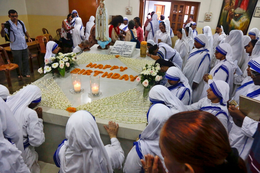 Nuns of the Missionaries of Charity, the order founded by Mother Teresa, pray by her tomb on her birth anniversary in Kolkata, India, Monday, Aug. 26, 2019. Mother Teresa received more than 120 honours and awards during her lifetime including the Ramon Magsaysay Peace Prize in 1962 and Nobel Peace Prize in 1979. (AP Photo/Bikas Das)