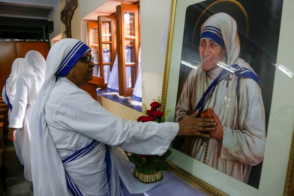 Nuns of the Missionaries of Charity, the order founded by Mother Teresa, pray in front of her portrait on her birth anniversary in Kolkata, India, Monday, Aug. 26, 2019. Mother Teresa was beatified on October 19 2003 and was known by Catholics as