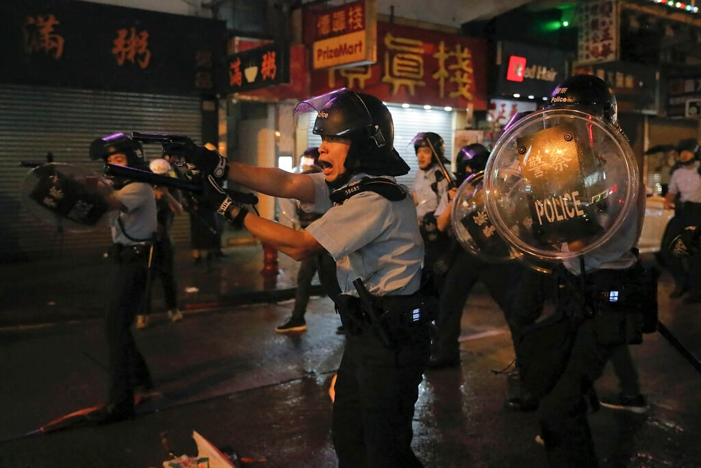 In this Sunday, Aug. 25, 2019, file photo, policemen pull out their guns after a confrontation with demonstrators during a protest in Hong Kong. Hong Kong police have rolled out water cannon trucks for the first time in this summer's pro-democracy protests. The two trucks moved forward with riot officers Sunday evening as they pushed protesters back along a street in the outlying Tsuen Wan district. (AP Photo/Vincent Yu, File)