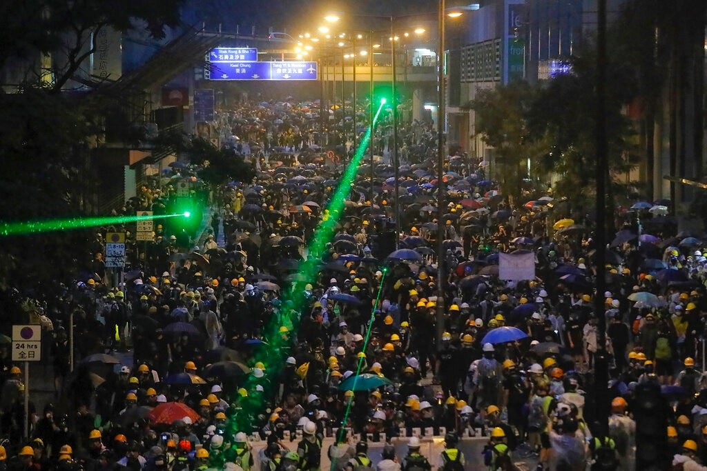 In this Sunday, Aug. 25, 2019, file photo, demonstrators, some using laser pointers toward police lines during a protest in Hong Kong. Hong Kong police have rolled out water cannon trucks for the first time in this summer's pro-democracy protests. The two trucks moved forward with riot officers Sunday evening as they pushed protesters back along a street in the outlying Tsuen Wan district. (AP Photo/Kin Cheung, File)