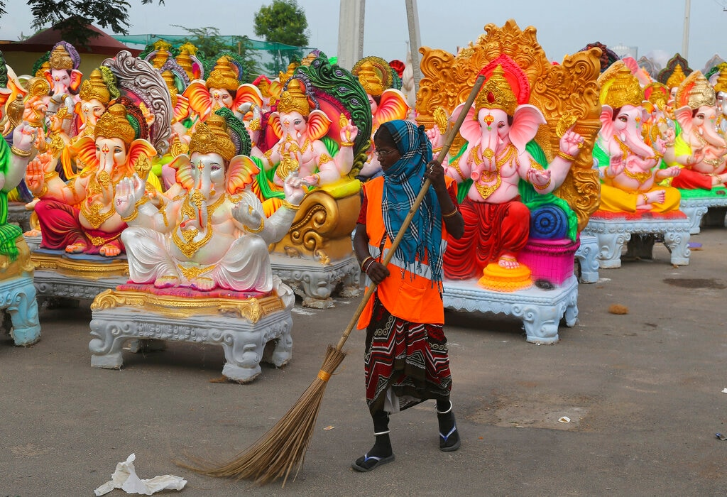 A woman sweeps a street in front of idols of Hindu god Ganesha being prepared ahead of Ganesha Chaturthi festival in Hyderabad, India, Thursday, Aug. 29, 2019. (AP Photo/Mahesh Kumar A.)