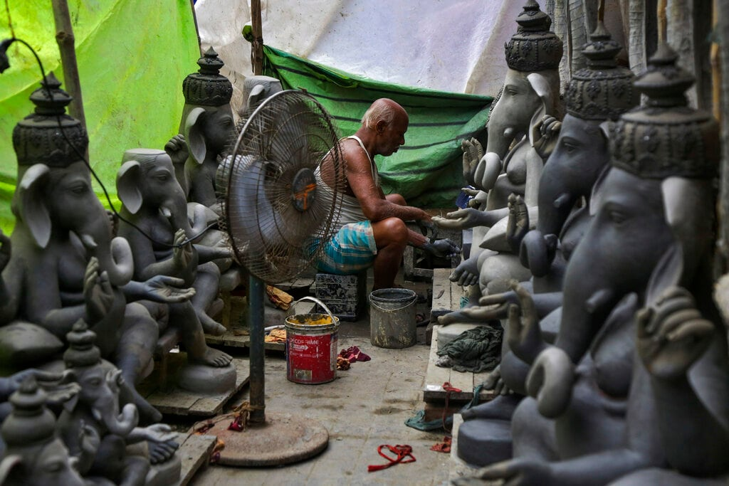 A pedestal fan is installed to quickly dry the idols as an elderly artisan makes clay idols of Hindu god Ganesh in a makeshift studio in Kolkata, India, Thursday, Aug. 29, 2019. The idols are being prepared for the upcoming Ganesh Chaturti festival. (AP Photo/Bikas Das)