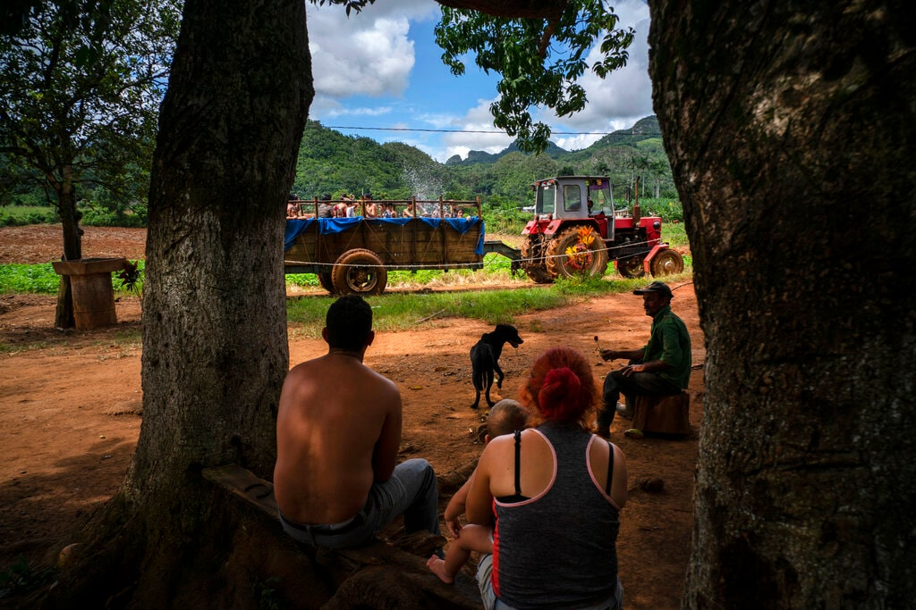 A family sitting in the shade watches as a tractor that pulls a trailer-turned-pool where children swim, drives past outside their home in the El Infernal neighborhood of San Andres in Cuba's province Pinar del Río, on Saturday, Aug. 24, 2019. The multi-use tractor in El Infernal isn't just used for farm work and a mobile pool, it's also occasionally pressed into service as an ambulance in an area with few motor vehicles. (AP Photo/Ramon Espinosa)
