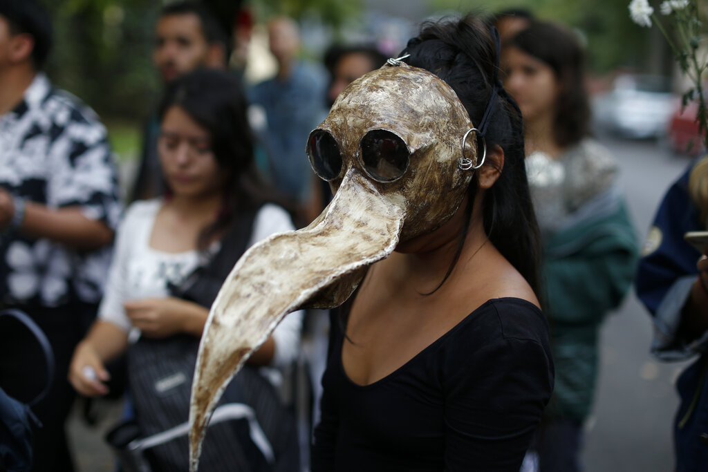 Medical student and environmentalist Sofia Guzman, 22, wears a mask she made to represent a toucan skull, during a protest to call for action to protect the Amazon rainforest, outside the Brazilian Embassy in Mexico City, on Friday, Aug. 23, 2019. Under increasing international pressure to contain fires sweeping parts of the Amazon, Brazil's President Jair Bolsonaro on Friday authorized use of the military to battle the massive blazes. (AP Photo/Rebecca Blackwell)