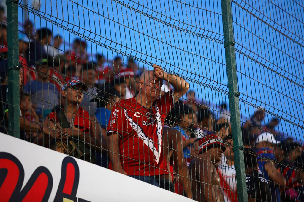 A dejected fan of the Veracruz Tiburones Rojos soccer team leans his head on the fence during a Mexican soccer league match against Queretaro in Veracruz, Mexico, on Tuesday, Aug. 27, 2019. Veracruz lost 5-0 to Queretaro on Tuesday night in the seventh round of the Apertura tournament to extend its winless run to 33 games, breaking the tie with the English club, which set the previous mark in the 2007-08 season. (AP Photo/Felix Marquez)
