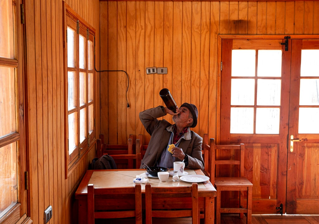 A man chugs a bottles of black beer while eating breakfast at a restaurant in Paine, Chile, on Friday, Aug. 23, 2019. (AP Photo/Esteban Felix)