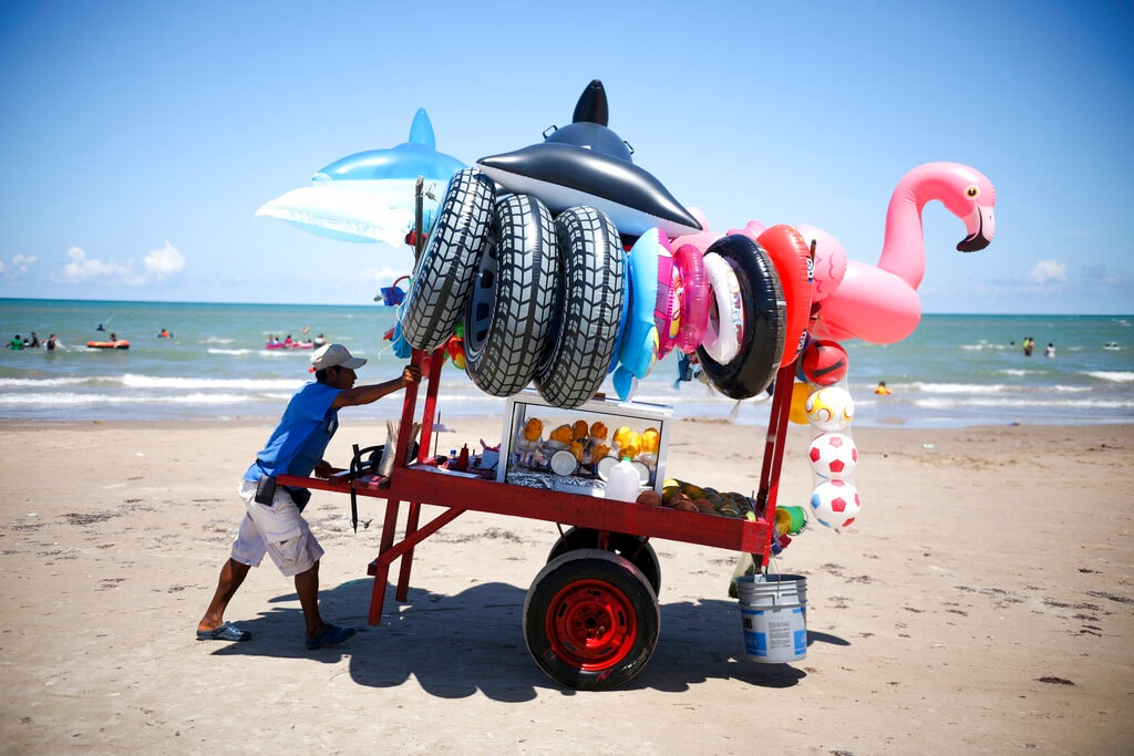 A vendor pushes his mobile cart equipped with inflatable pool toys and fruit cups along the shoreline of Playa Bagdad near the border city of Matamoros, Mexico, on Saturday, Aug. 3, 2019. At the very eastern end of the U.S.-Mexico border there's a long strip of sand where the Rio Grande meets the sea. It is called Playa Bagdad. Here there are no steel pilings marching out to sea to stop migrants from swimming, wading or paddling across to the United States. (AP Photo/Emilio Espejel)