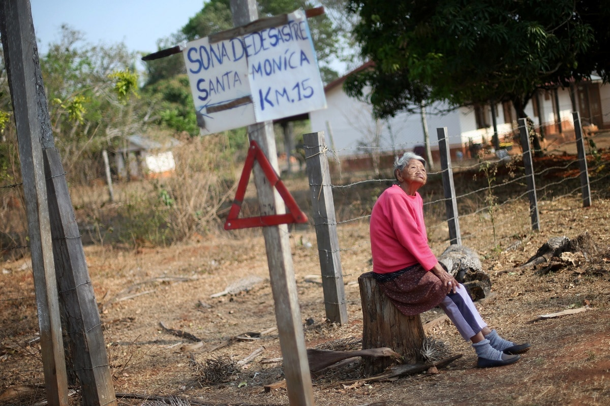 A resident looks on in Santa Monica community in Concepcion, Bolivia. The sign reads,