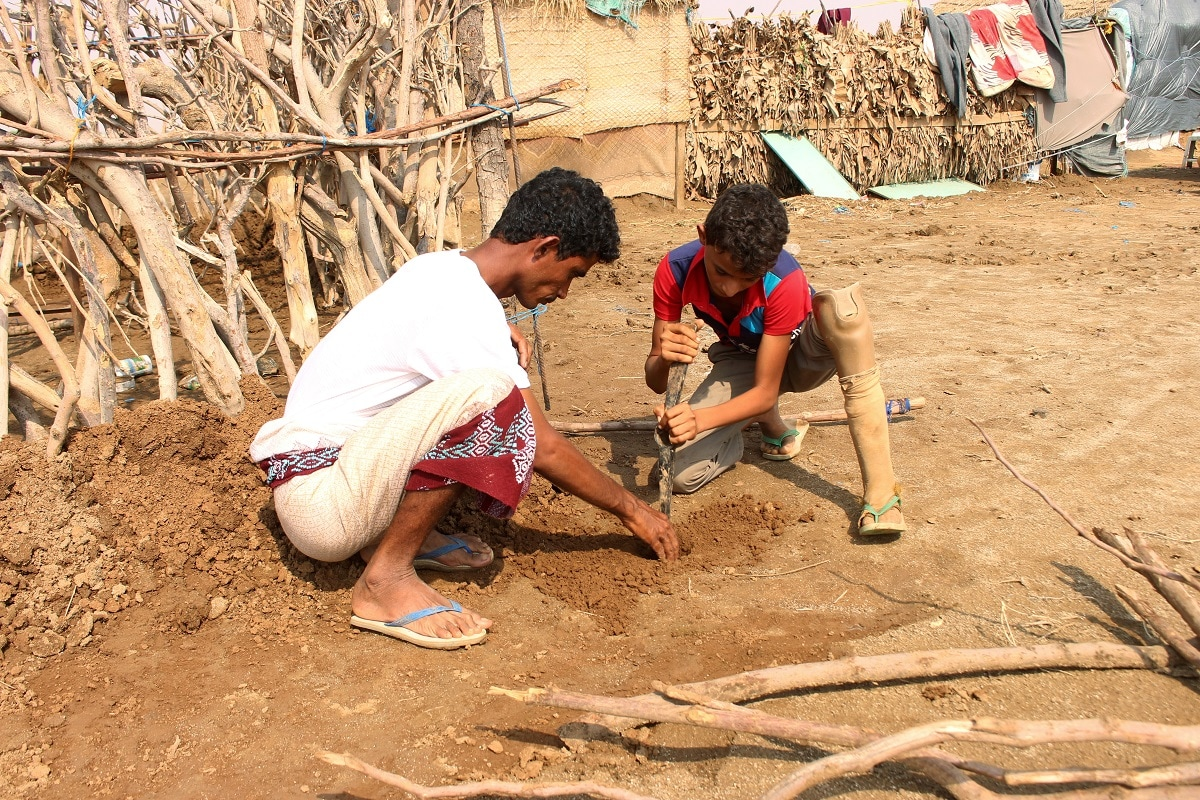 Ismail Abdullah (R), 12, who lost his leg in an airstrike two years ago, helps his brother build a hut at a camp for internally displaced people in Khamis. REUTERS/Eissa Alragehi