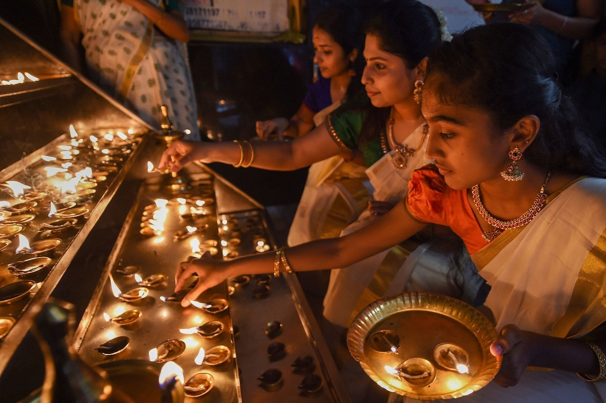 Women light lamps at a temple during Onam celebrations. (PTI Photo)