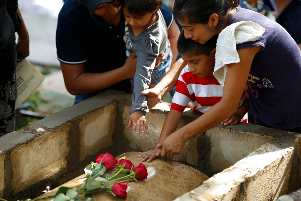 Family members pay their last respects to Maria del Carmen Segovia Padua as they prepare to bury her alongside her aunt Zuleyma Hernandez Sanchez at the municipal cemetery in Coatzacoalcos, Veracruz state, Mexico, Thursday, August 29, 2019. Mexico's President Andres Lopez Obrador insists his go-slow policies of reducing youth unemployment will eventually solve the root causes of violent crime better than declaring another frontal offensive against drug cartels. (AP Photo/Rebecca Blackwell)