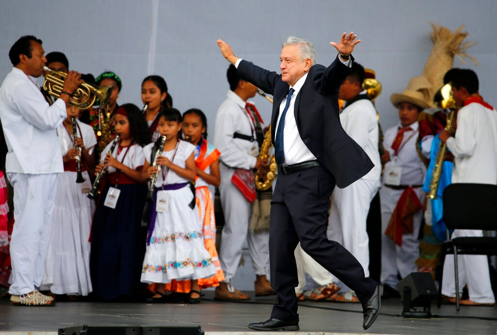 In this July 1, 2019 file photo, Mexico's President Andres Manuel Lopez Obrador greets supporters as he arrives at a rally to celebrate the one-year anniversary of his election, in Mexico City's main square, the Zocalo. Lopez Obrador's high approval ratings topped 70 percent in some polls nine months into his term. Many Mexicans are willing to give Lopez Obrador the benefit of the doubt as even the president acknowledges that violent crime is the most serious challenge he faces. (AP Photo/Fernando Llano, File)