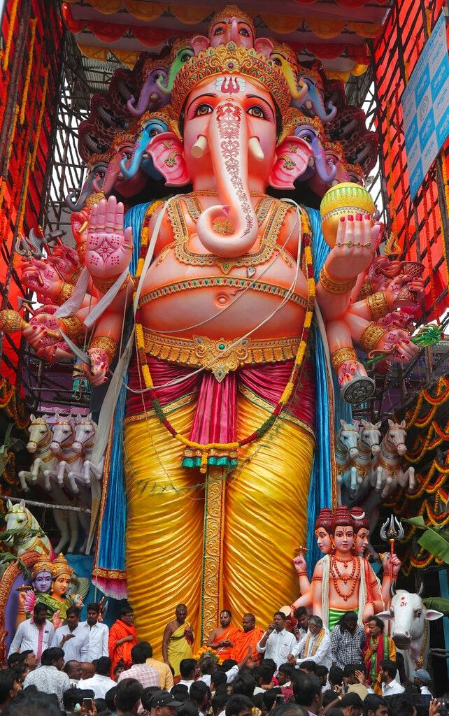 Hindu devotees worship a huge idol of elephant-headed Hindu god Ganesha during Ganesh Chaturthi festival in Hyderabad, India, Monday, September 2, 2019. The ten-day long festival, that celebrates the birth of the Hindu god of wisdom, prosperity and good fortune, ends Sunday. (AP Photo/Mahesh Kumar A.)