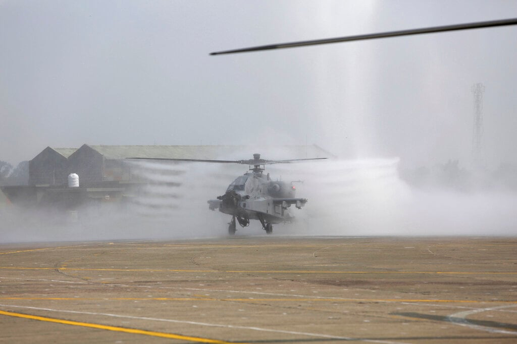 An AH-64E Apache helicopter is sprayed with water during its induction ceremony into the Indian Air Force at the Pathankot air force station, on Tuesday. (AP Photo/Channi Anand)