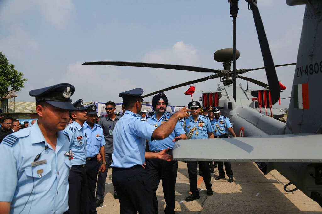 Indian Air Force chief BS Dhanoa, center wearing turban, inspects a AH-64E Apache helicopter during its induction ceremony into the Indian Air Force at the Pathankot Air Force Station, on Tuesday. (AP Photo/Channi Anand)