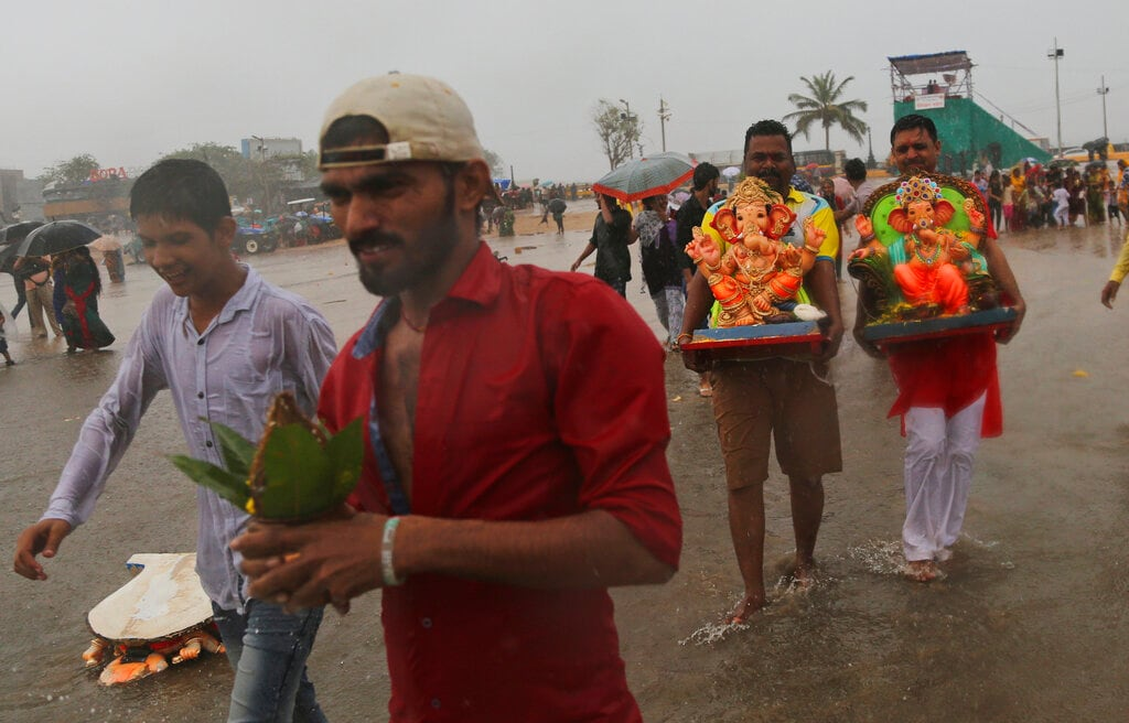 Devotees carry idols of elephant-headed Hindu god Ganesha for immersing it in the Arabian Sea on the second day of the ten-day long Ganesh Chaturthi festival in Mumbai, India, on Tuesday. The festival is a celebration of the birth of Ganesha, the Hindu god of wisdom, prosperity and good fortune. (AP Photo/Rafiq Maqbool)