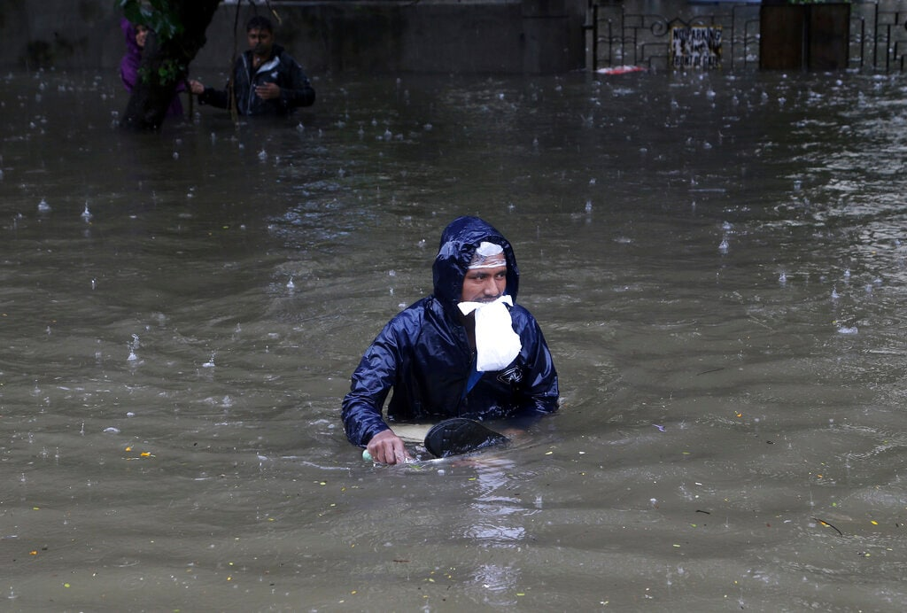 A man holds a packet between his teeth and navigates his way through a flooded street. (AP Photo/Rajanish Kakade)