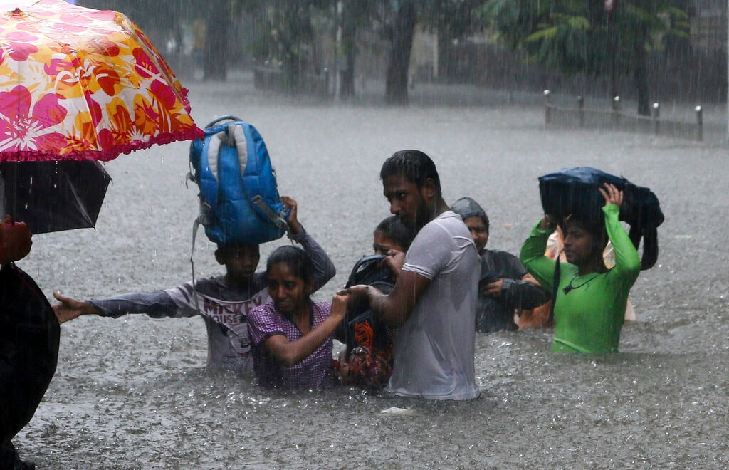People navigate their way through a flooded street. (AP Photo/Rajanish Kakade)