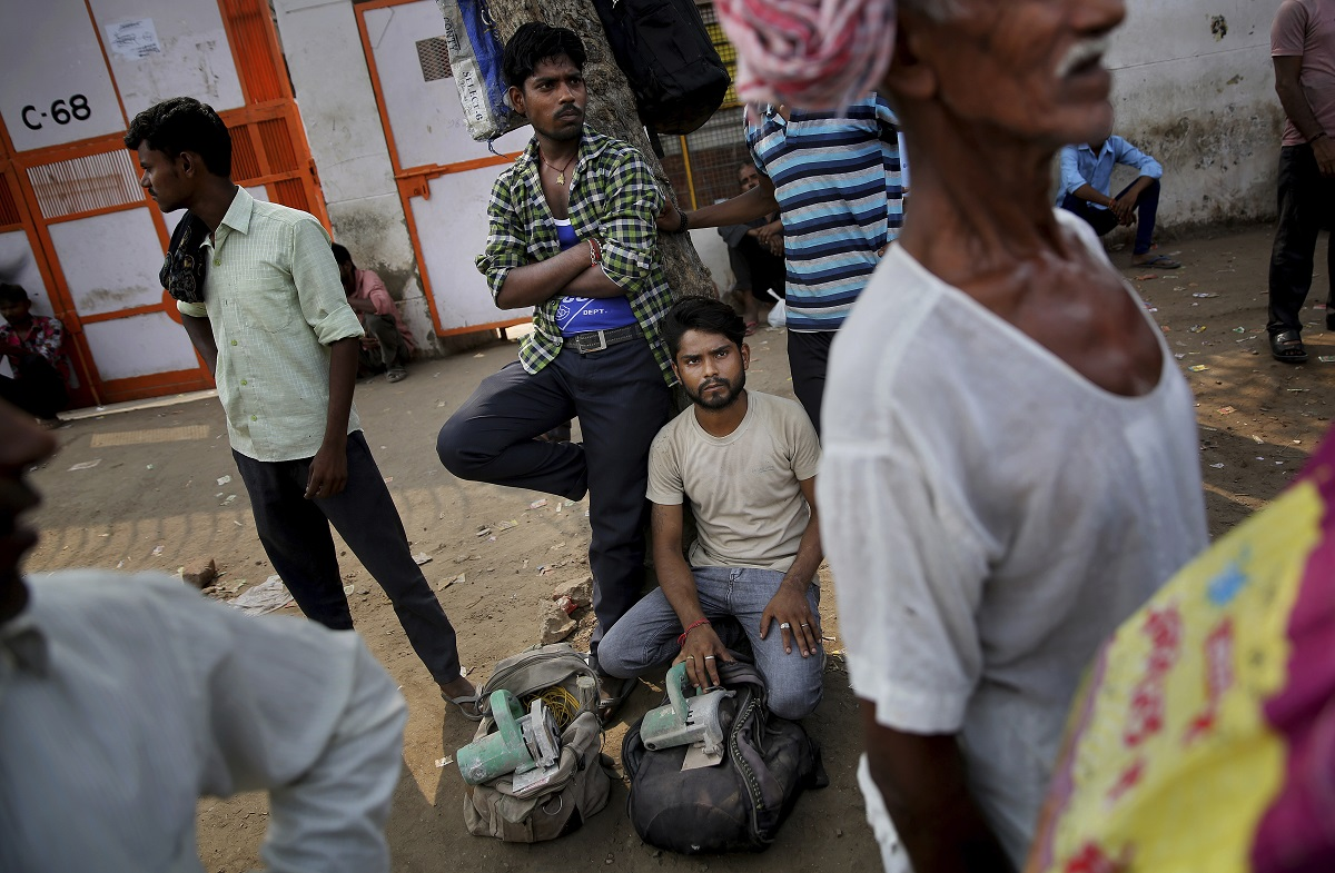 Daily wage labourers and construction workers wait to get hired on the outskirts of New Delhi. (AP Photo/Altaf Qadri)