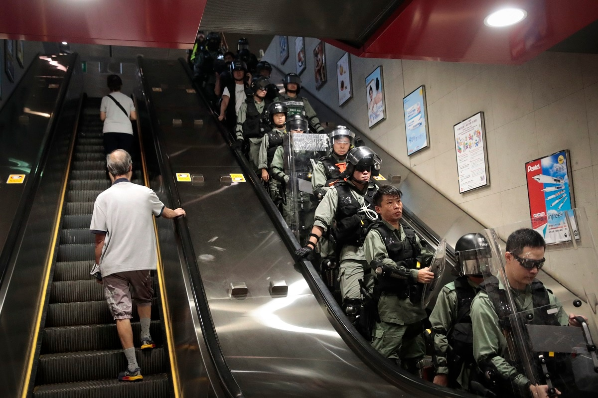Commuters ride an escalator at a train station past police officers in riot gear deployed to arrest protesters in Hong Kong. Life is not quite normal after three months of steady protests in the Asian financial centre - and yet normal life goes on, as it must, for the city's 74 lakh residents. (AP Photo/Jae C. Hong)