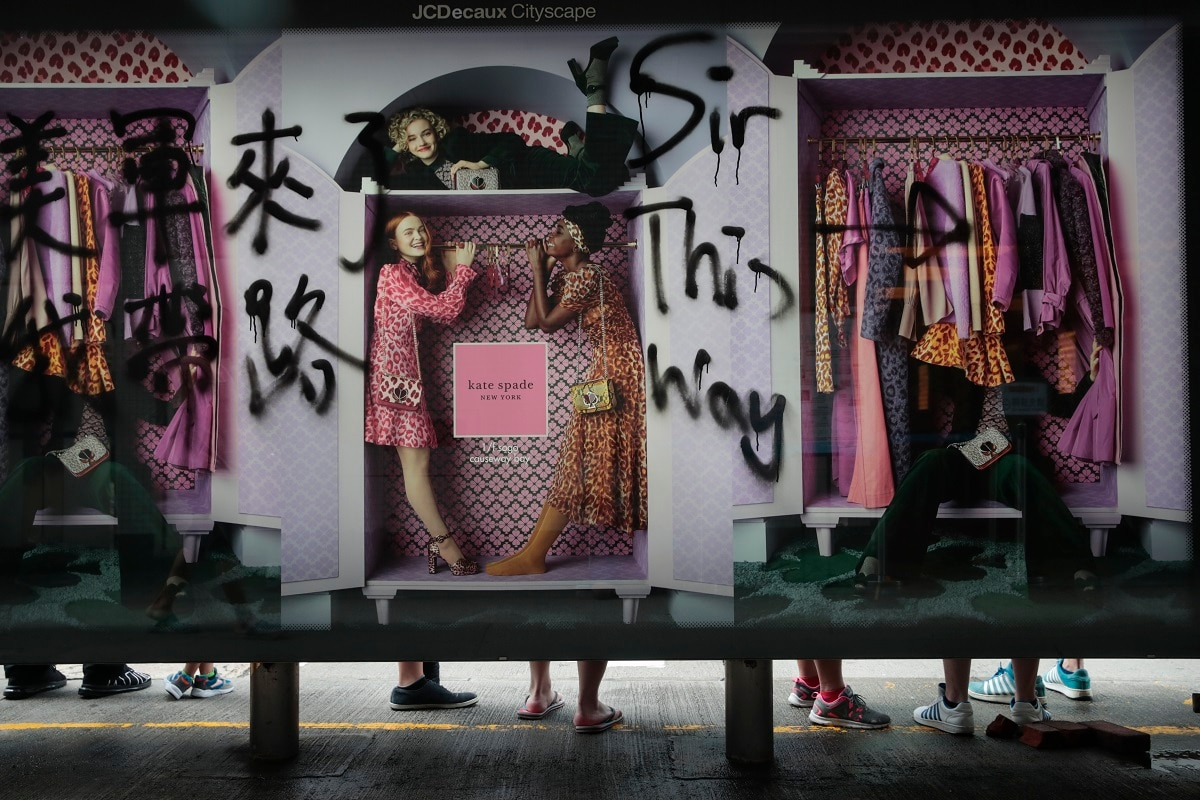 People wait for buses at a bus stop vandalized by protesters in Hong Kong. (AP Photo/Jae C. Hong)