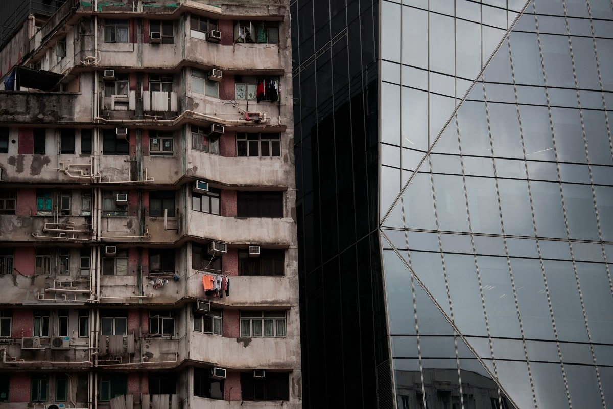 An old apartment building stands next to a gleaming tower in Hong Kong. (AP Photo/Jae C. Hong)