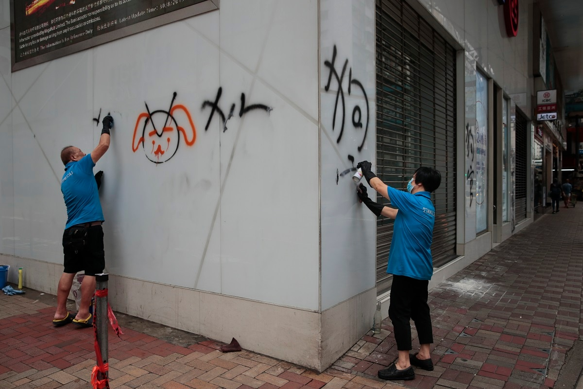 Workers remove graffiti left by protesters during a protest the night before in Hong Kong.  (AP Photo/Jae C. Hong)