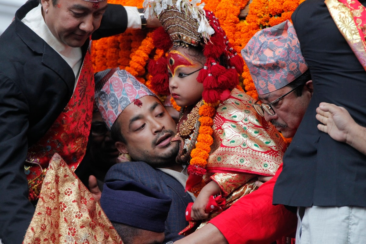 A devotee carries a revered living goddess Kumari, centre, to a chariot during Indra Jatra festival. The living goddess was pulled around the main parts of the capital Friday by devotees on a wooden chariot as tens of thousands of people lined up the old city to get a glimpse and blessing. (AP Photo/Niranjan Shrestha)