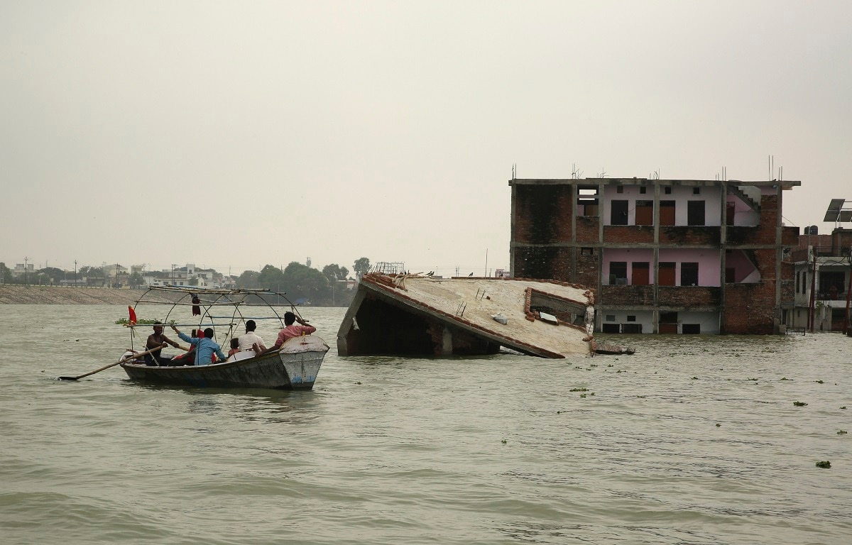 People move on boats past submerged houses by the River Ganges in Prayagraj. Heavy monsoon rains have raised the water levels of the Ganges River above the danger level, triggering an evacuation of thousands of people from flooded homes around the area. (AP Photo/Rajesh Kumar Singh, File)
