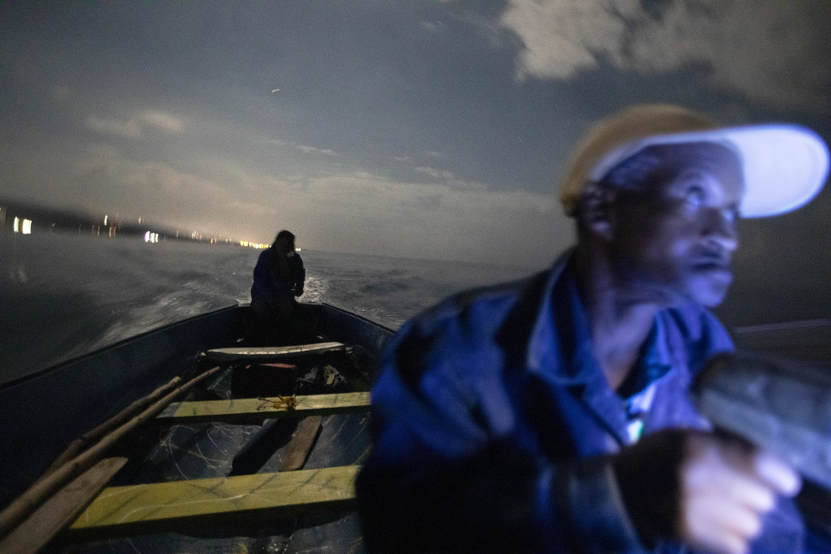White River Fish Sanctuary wardens Mark Lobban, left, and Donald Anderson patrol the no-take zone for illegal fishermen under the moonlight in Ocho Rios, Jamaica. Two years ago, fishermen joined with local businesses to form a marine association and negotiate the boundaries for a no-fishing zone stretching two miles along the coast. A simple line in the water is hardly a deterrent, however, for a boundary to be meaningful, it must be enforced. (AP Photo/David Goldman)
