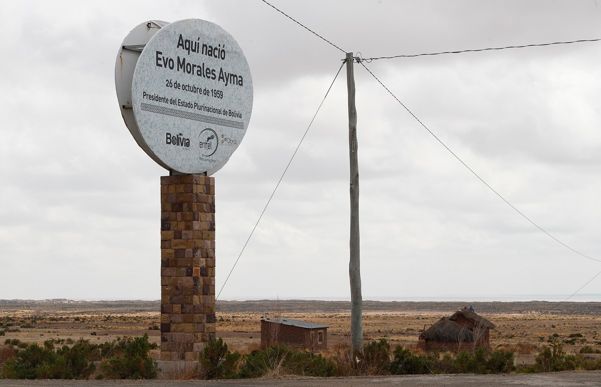 This photo shows a towering stone post topped with a round billboard pointing out the straw roof home where Bolivia's President Evo Morales was born, on the outskirts of Orinoca, Bolivia. The two-room adobe house still has a thatched roof. It's locked under bolt and its windows are boarded over. It's the home where Morales was born and lived until age 15. (AP Photo/Juan Karita)