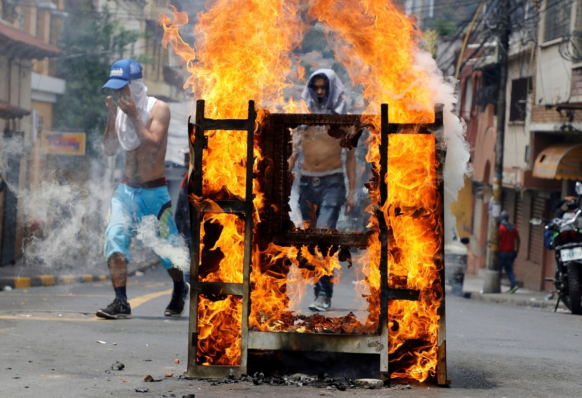 A demonstrator blocks a street during a protest demanding the resignation of President Juan Orlando Hernandez, in Tegucigalpa, Honduras. Hernández has suffered a credibility crisis since Honduras' Supreme Court cleared the way for his re-election despite a constitutional ban. His subsequent 2017 election win was marred by irregularities. (AP Photo/Elmer Martinez)