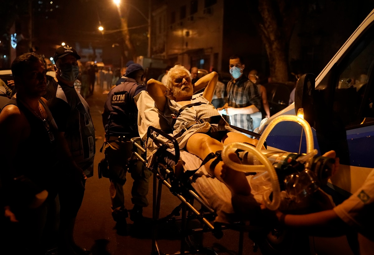 Patients are evacuated from a burning hospital in Rio de Janeiro, Brazil. The fire forced staff to hastily evacuate patients and temporarily settle some on sheets and mattresses in the street while firefighters fought the blaze. (AP Photo/Leo Correa)